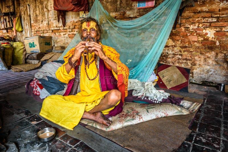 Sadhu baba (holy man) plays a pipe in Pashupatinath Temple, Nepal stock photo