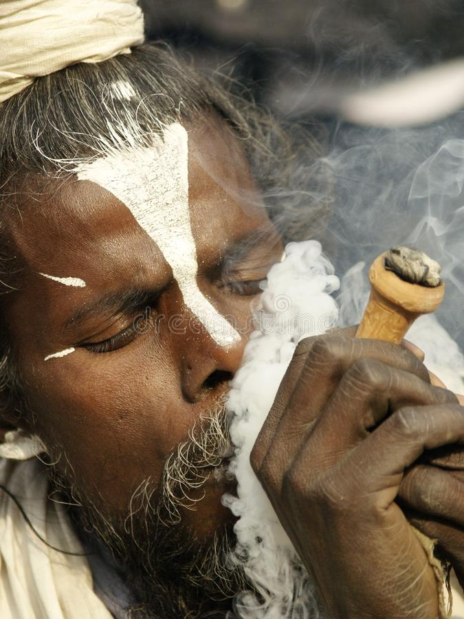 Sadhu ett helgon som tycker om marijuana i den Shivaratri festivalen royaltyfri foto