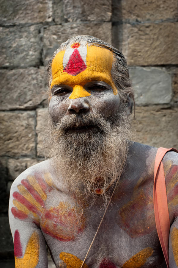 Sadhu man, blessing in Pashupatinath Temple. KATHMANDU, NEPAL, PASHUPATINATH TEMPLE - SEPTEMBER 21: Holy Sadhu man with traditional painted face, blessing in stock photo