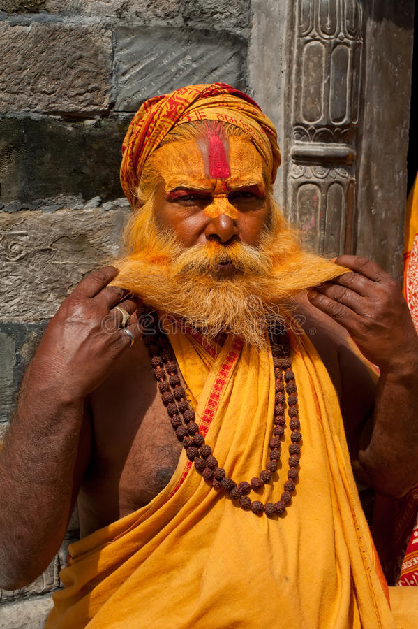 Sadhu man, blessing in Pashupatinath Temple. KATHMANDU, NEPAL, PASHUPATINATH TEMPLE - SEPTEMBER 21: Holy Sadhu man with traditional painted face, blessing in royalty free stock images