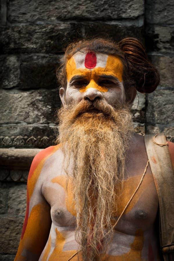 Sadhu man, blessing in Pashupatinath Temple. KATHMANDU, NEPAL, PASHUPATINATH TEMPLE - SEPTEMBER 21: Holy Sadhu man with traditional painted face and dreadlocks royalty free stock photography