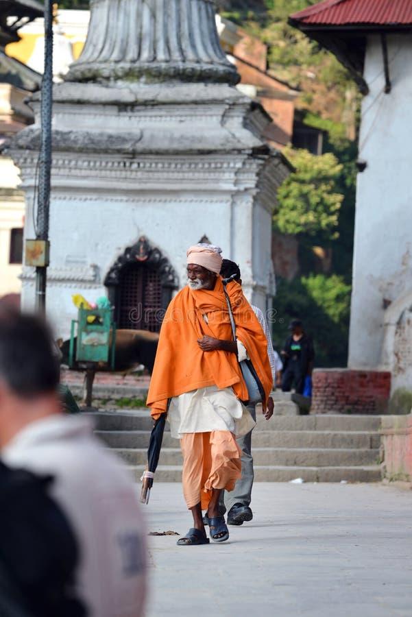Sadhu man at the holy Hindu temple of Pashupatinath. Nepal. KATHMANDU - OCT 8: Nepalese Sadhu man seeking alms at Pashupatinath Temple. Tourism has drawn many stock photo