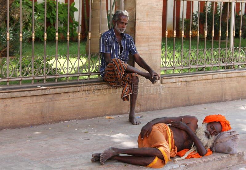 Sadhu o una persona santa indù che dorme con l'abito arancio che dorme sulla via fotografia stock