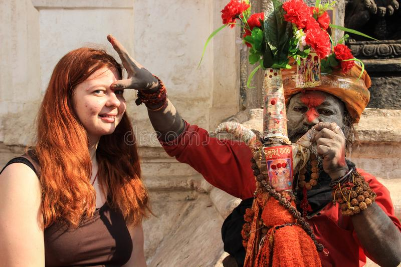 Sadhu paints the forehead of female tourist girls with red teak paint royalty free stock image