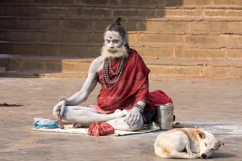 Sadhu sitzt auf dem ghat entlang dem Ganges in Varanasi, Indien lizenzfreie stockbilder