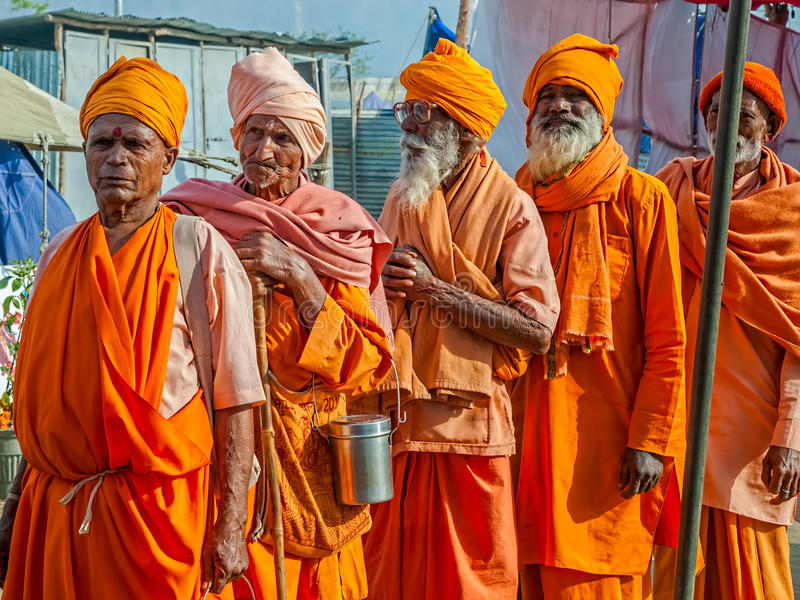 Sadhus in Haridwar. HARIDWAR, INDIA - APRIL 12, 2010: Sadhus pilgrims waiting in line for lunch, dressed in orange clothes on the Kumbh Mela - is a mass Hindu stock image