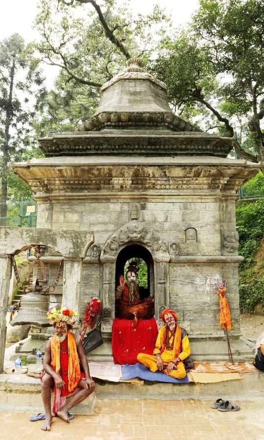 Sadhus in a temple near Sri Pashupatinath Temple. KATHMANDU, NEPAL-AUGUST 21: Sadhus sitting in a shrines near Pashupatinath temple on August 21, 2014, Kathmandu stock photos
