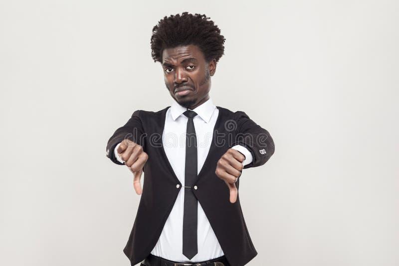 Sadness afro man showing dislike and looking at camera. Studio shot, gray background royalty free stock photo