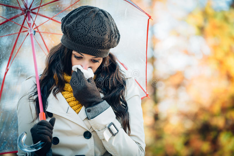 Sadness flu and cold on autumn. Sad woman with cold or flu blowing her nose with a tissue under autumn rain. Brunette female sneezing and wearing warm clothes royalty free stock image