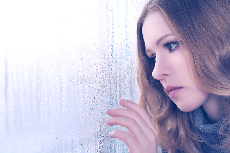Sadness girl at the window in the rain. Sad girl is bored and sadness at the window in the rain royalty free stock photos