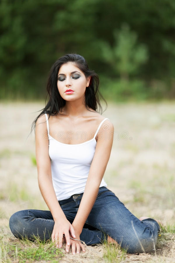 Sadness. Sad attractive girl sitting on the meadow royalty free stock photography