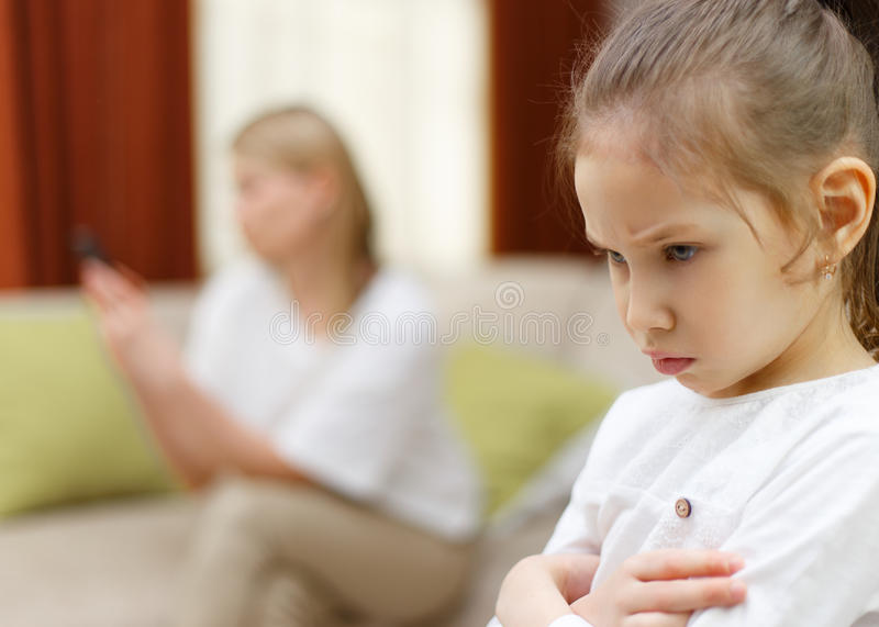 Sadness young girl. Portrait of bored daughter with mother using cellphone on bed. royalty free stock photography