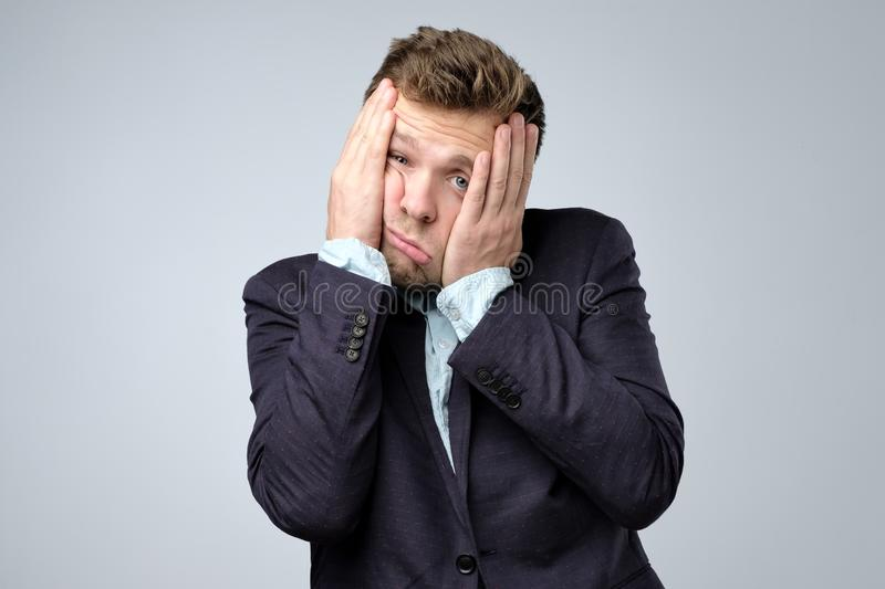 Sads young business man in suit, white shirt putting hand on head on grey wall background in studio royalty free stock image
