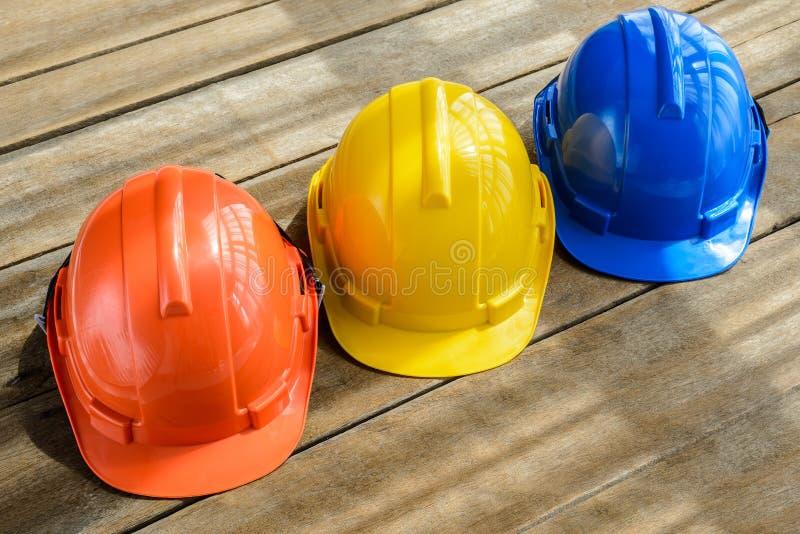 saf的蓝色,橙色,黄色坚硬安全帽建筑帽子 库存图片