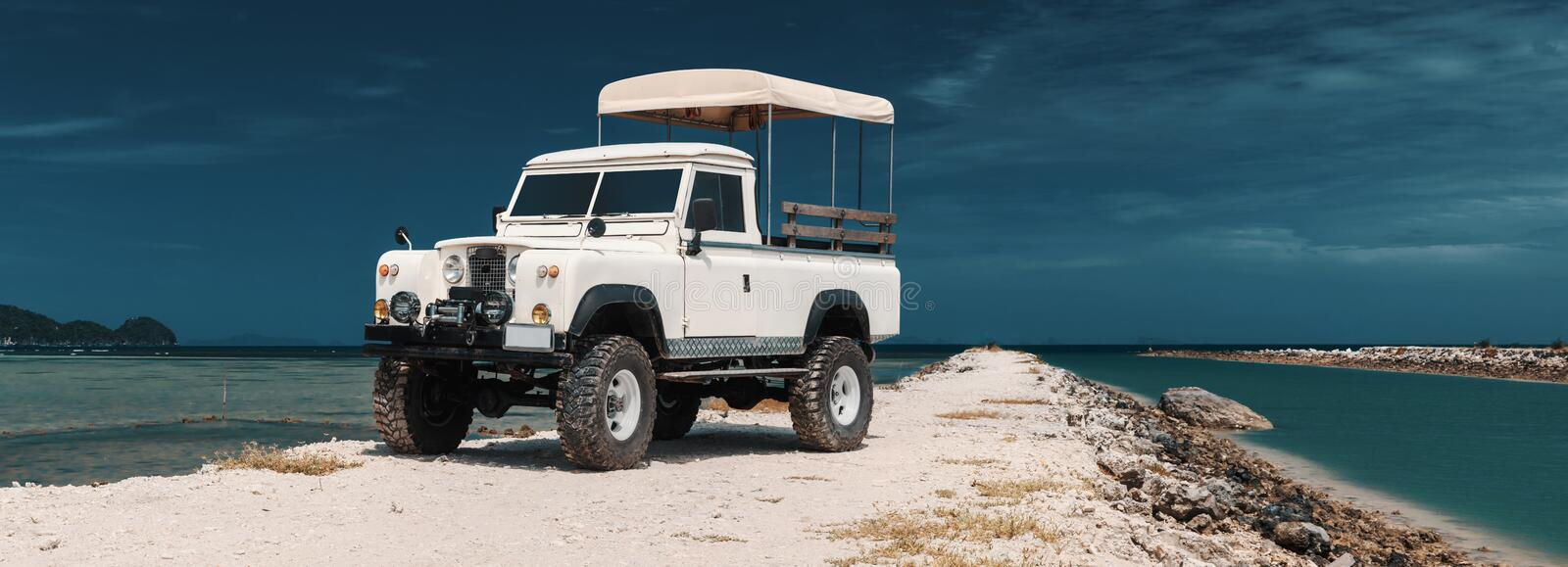 Safari car on offroad ,adventure trail. Panoramic photo of safari car on offroad , adventure trail. ocean, sky and clouds on background, With empty space for stock photos