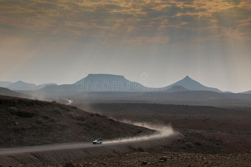 Safari car traveling fast through a scenic landscape. In africa, namibia stock photo