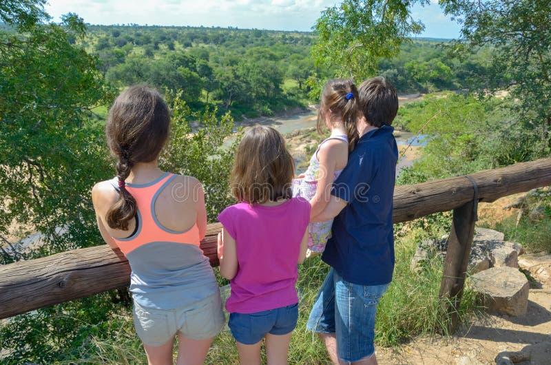 Safari de la familia en África, los padres y los niños mirando la fauna y la naturaleza, viaje turístico del río en Suráfrica, pa fotos de archivo