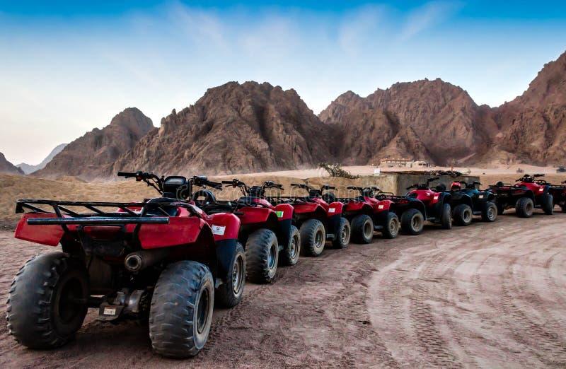 Safari de Moto en el desierto una fila de ATVs rojo en un alto contra la perspectiva de montañas rocosas y de un cielo azul Egipt imagen de archivo