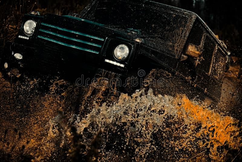 Safari suv. Off-road vehicle goes on mountain way. Offroad vehicle coming out of a mud hole hazard. Mudding is off. Roading through an area of wet mud or clay royalty free stock photography