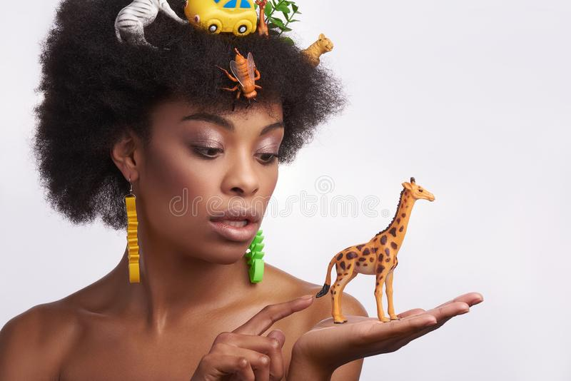 Curious ethnic lady hold giraffe toy on hand royalty free stock photography