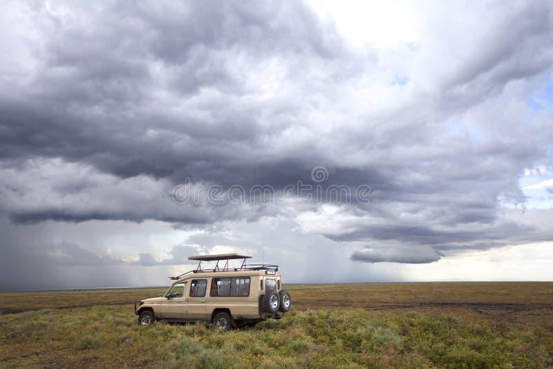 Safariauto in de serengetimara savanne vóór onweersbui stock afbeeldingen