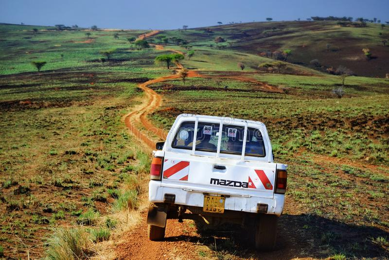Safarijeep die zich in een stoffige weg in de steppe van Oost-Afrika bevinden stock fotografie