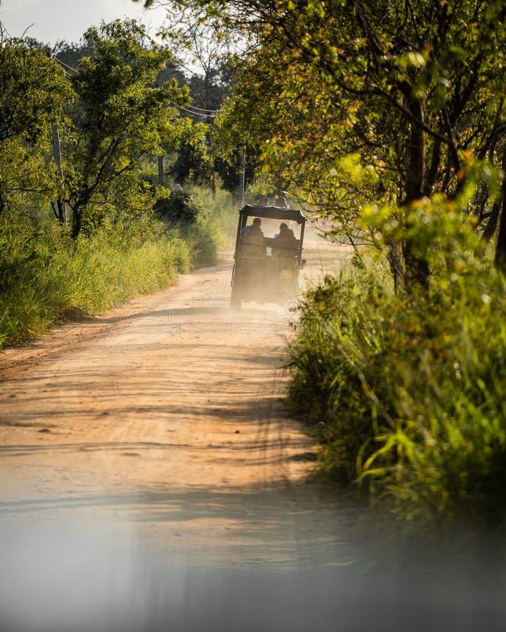 Safarijeep på en dammig grusväg royaltyfri foto