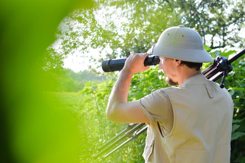 Safarireis: beeld van mannelijke toerist of het onderzoeken van wetenschapper in merghelm die pret waarnemen hebben die in vergro stock foto