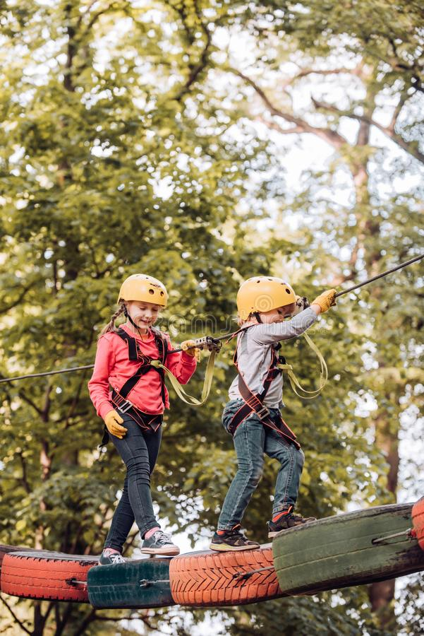 Safe Climbing extreme sport with helmet. Rope park. Cargo net climbing and hanging log. Cute school child boy enjoying a. Sunny day in a climbing adventure royalty free stock photography
