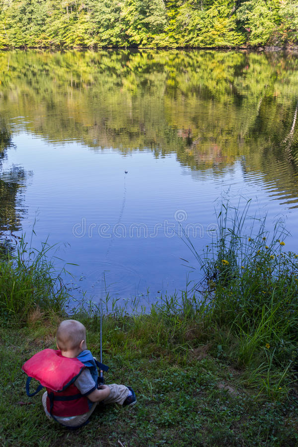 Safe fisherman. Young boy fishes from the bank wearing a life vest royalty free stock photo