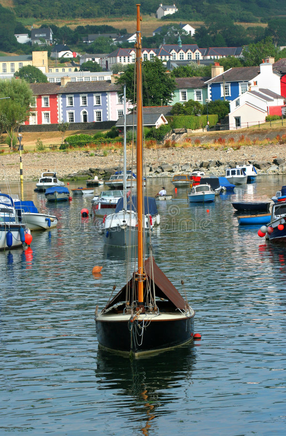 Safe Haven. Sailing boat with various small boats at anchor, in a fishing harbour with colorful houses to the rear. Location, Aberaeron, Wales, United Kingdom stock photo