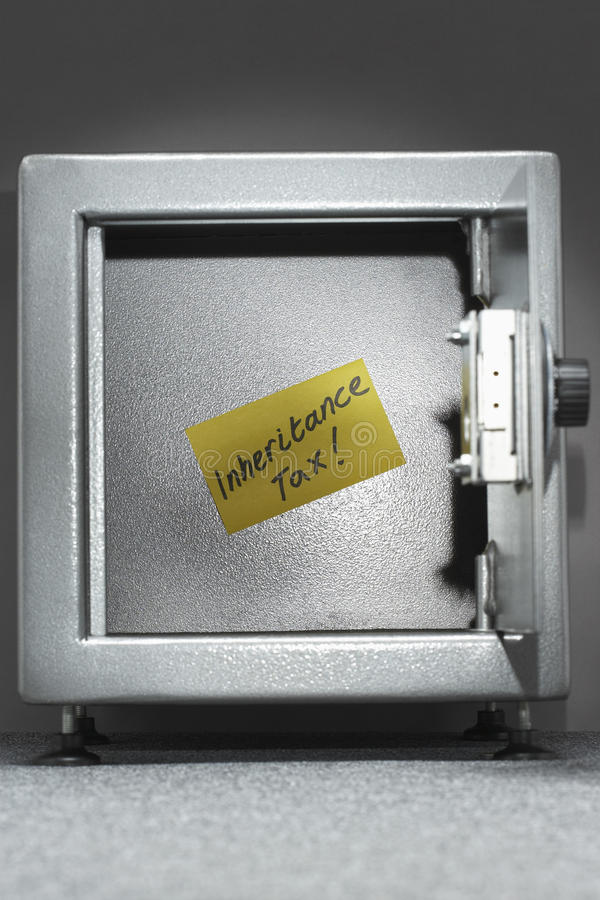 Safe with sticky note reading 'inheritance tax' royalty free stock photo