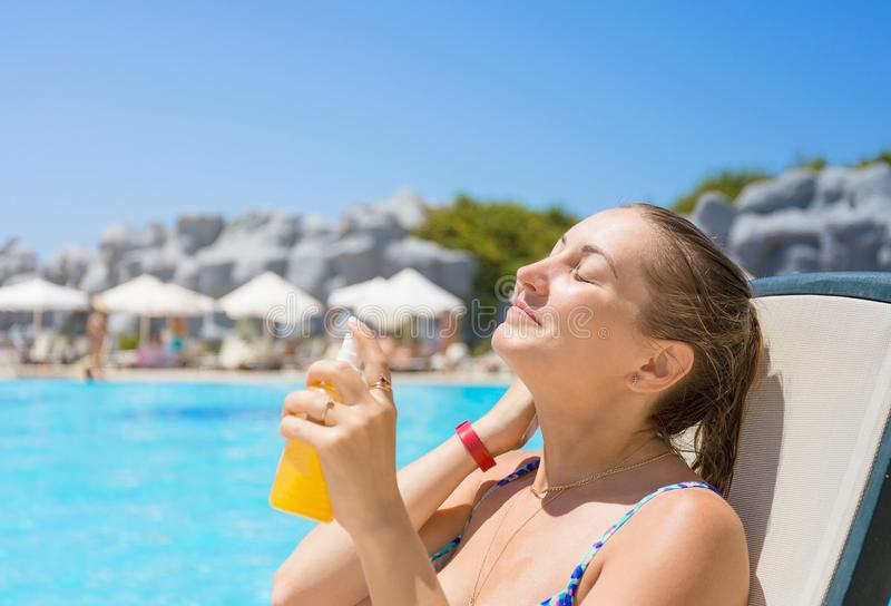 Safe sunbathing. Woman by the pool on vacation royalty free stock photos