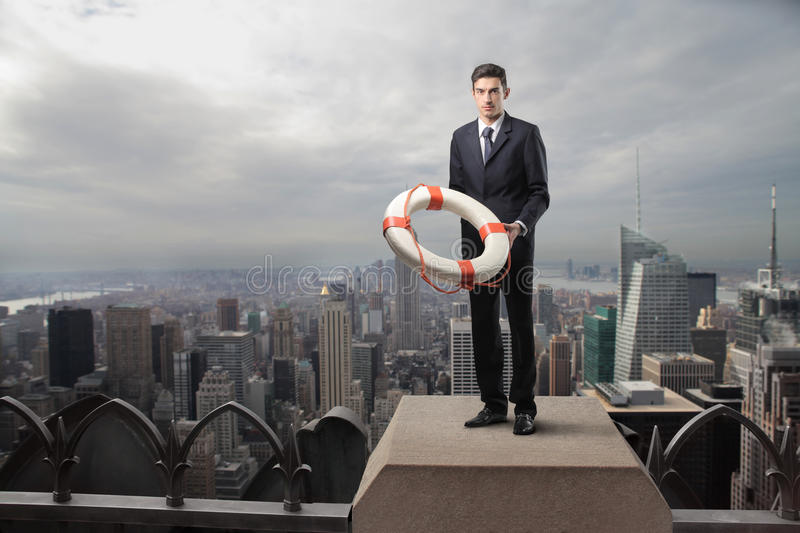 Safety. Businessman standing on the top of a skyscraper with a lifebelt in his hands stock photo