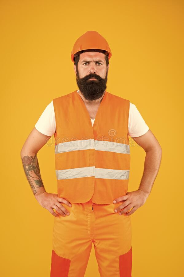 Safety apparel for construction industry. Bearded brutal hipster safety engineer. Man engineer protective uniform orange royalty free stock images