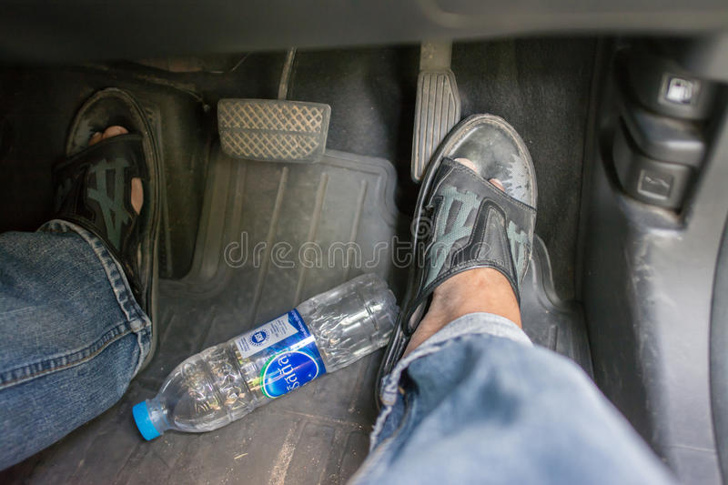 Safety. Bangkok, Thailand, July 30, 2017: A man is driving a car. And with a bottle of waterfall near his feet, the concept of safety should be taken off the royalty free stock photo
