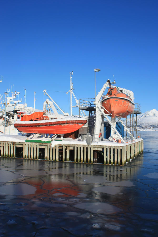 Safety boat and icy sea. Safety boat reflecting on the icy sea of Busknesfjord, Lofoten islands royalty free stock photos