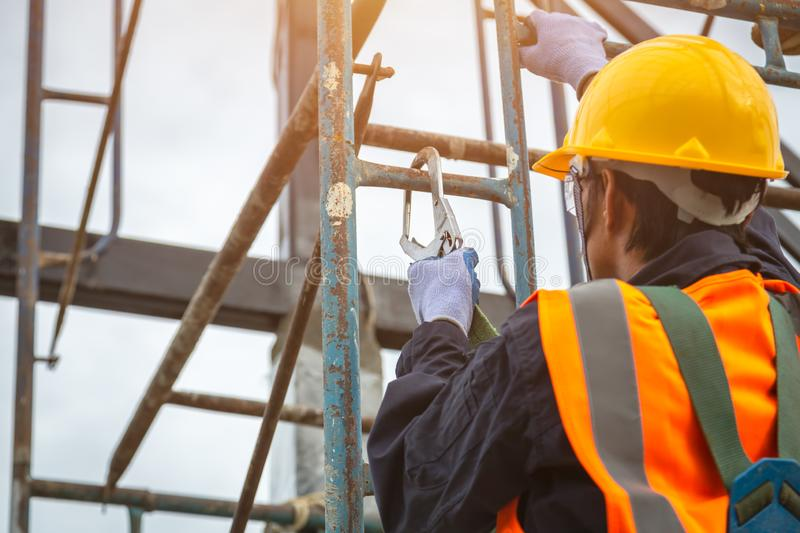 [safety body construction] Working at height equipment. Fall arrestor device for worker with hooks for safety body harness on. Selective focus. Worker as in royalty free stock image