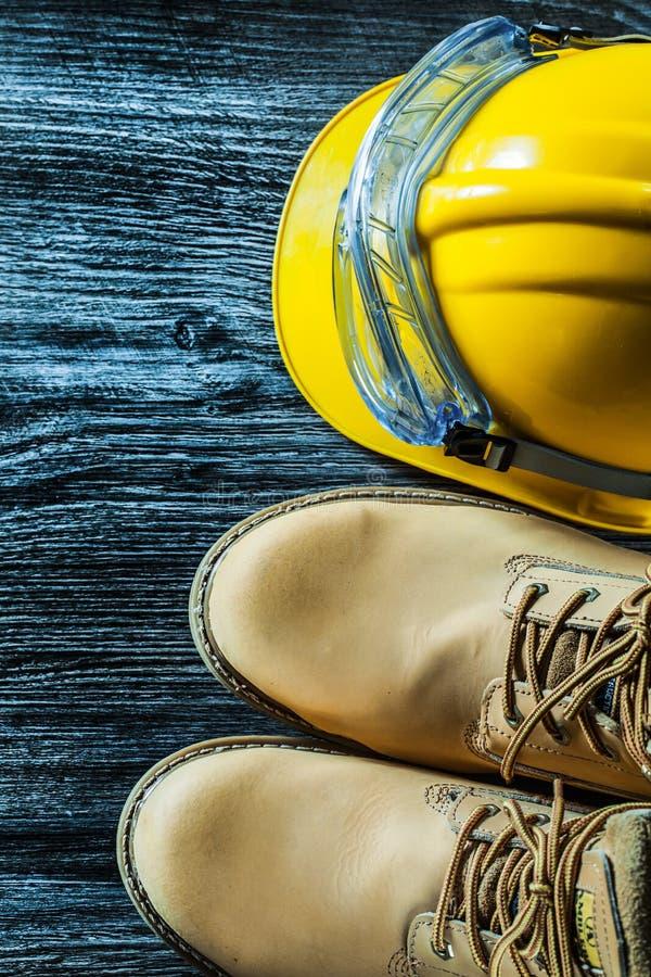 Safety boots glasses building helmet on vintage wooden board stock image