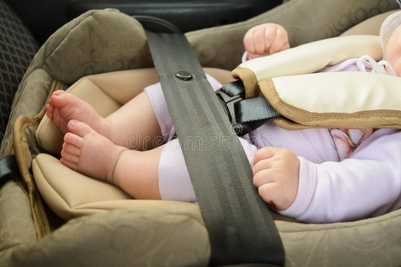 Safety concept, protection of child in travel, children feet in baby seat. Small baby sitting in special car seat with safety. Safety concept, protection of stock photography