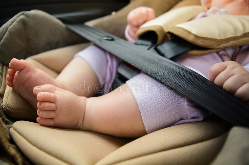 Safety concept, protection of child in travel, children feet in baby seat. Small baby sitting in special car seat with safety. Safety concept, protection of stock photo