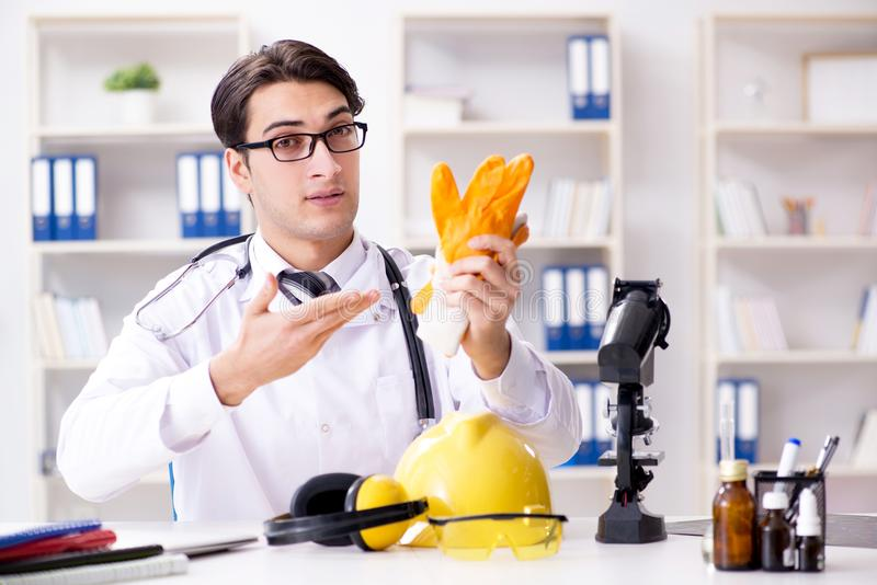 The safety doctor advising about wearing protective gloves stock image