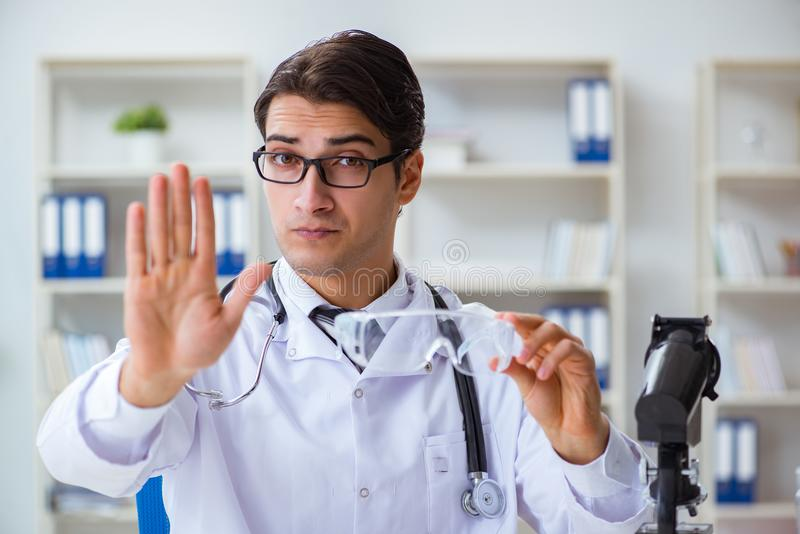The safety doctor advising about wearing protective goggles royalty free stock images