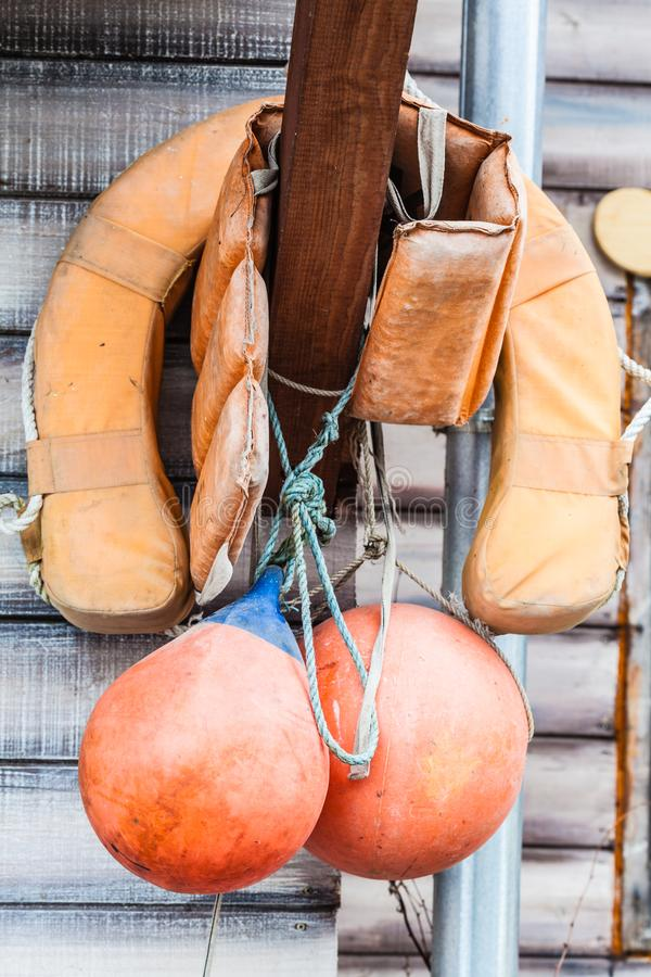 Orange life jacket and buoy hanging outside. Safety equipment concept. Orange life jacket and buoy hanging outside on wooden wall stock photos
