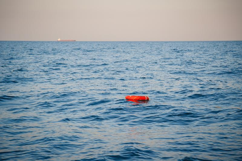 Safety equipment, life buoy or rescue buoy ring with a rope floating in blue sea to rescue people. Yachting, marine background stock images