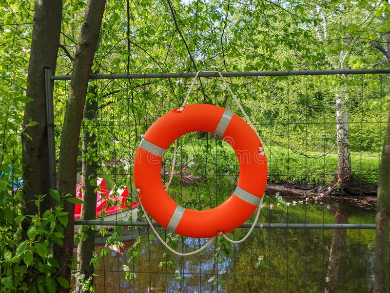 Safety equipment, lifebuoy or rescue buoy hanging on the fence near the boat station stock photos
