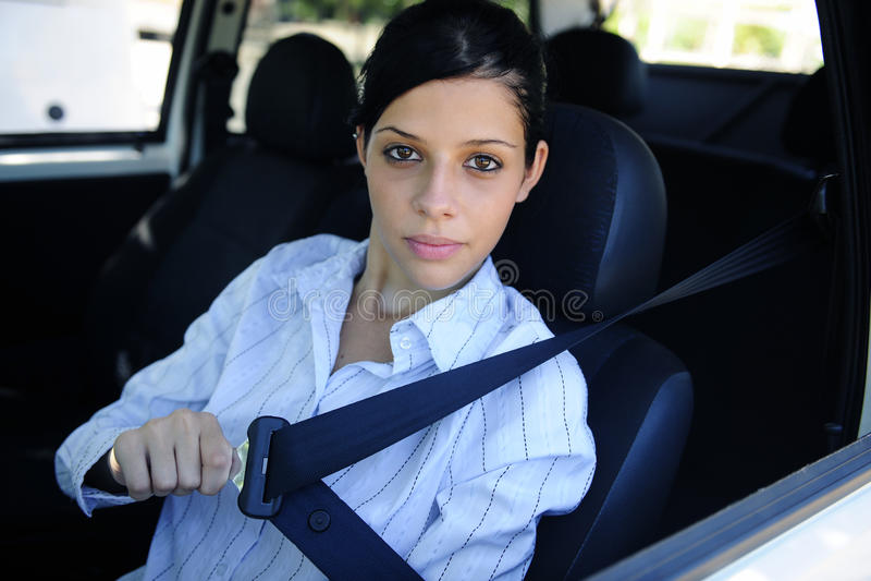 Safety: female driver fastening seat belt. Car safety: female driver fastening seat belt stock photos
