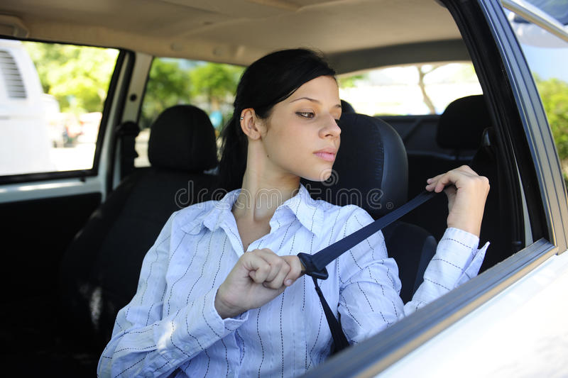 Safety: female driver fastening seat belt. Car safety: female driver fastening seat belt royalty free stock photography