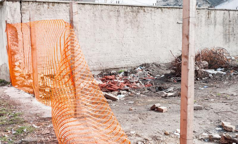 Construction site safety orange net or fence around of remains of hurricane or earthquake disaster damage on ruined old house sele. Safety fence, Construction stock image
