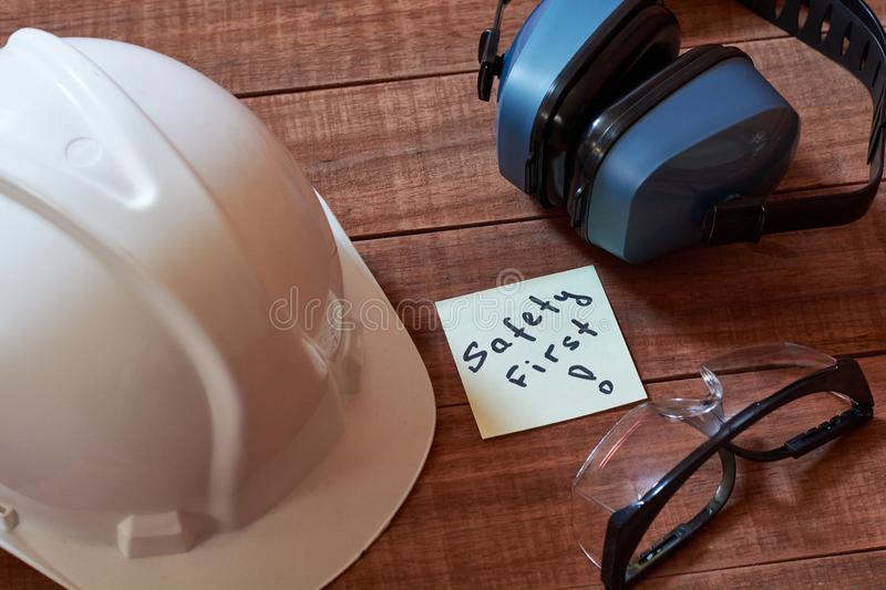 Safety first note one yellow piece of paper stuck on wooden background with full set of personal protective equipment: helmet, saf. Et glasses and ear protection stock photo